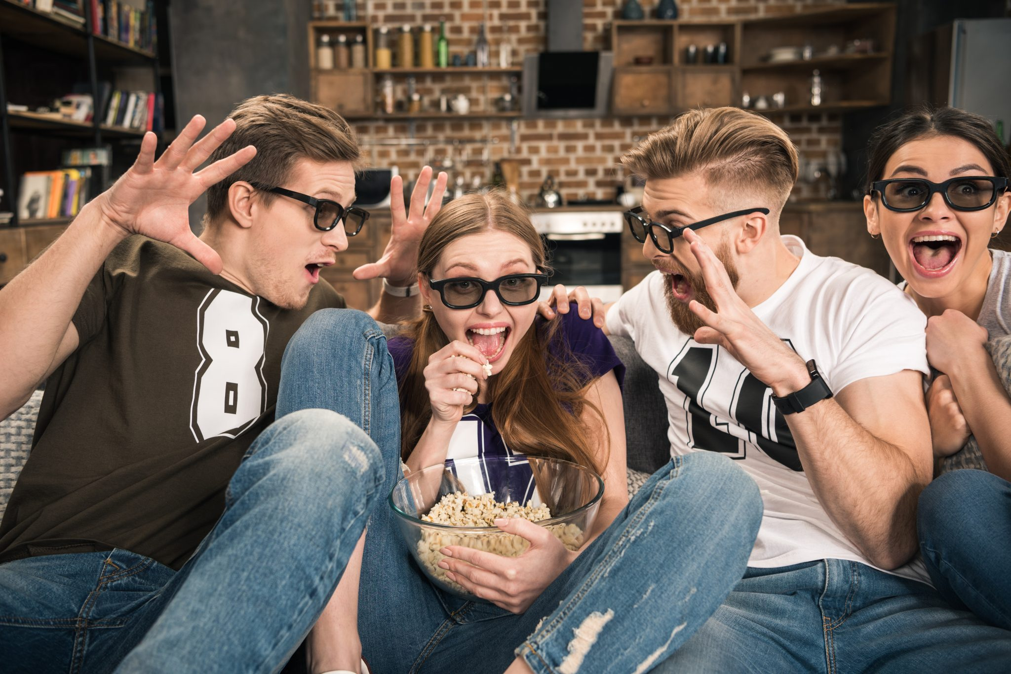 excited friends in 3D glasses watching movie at home